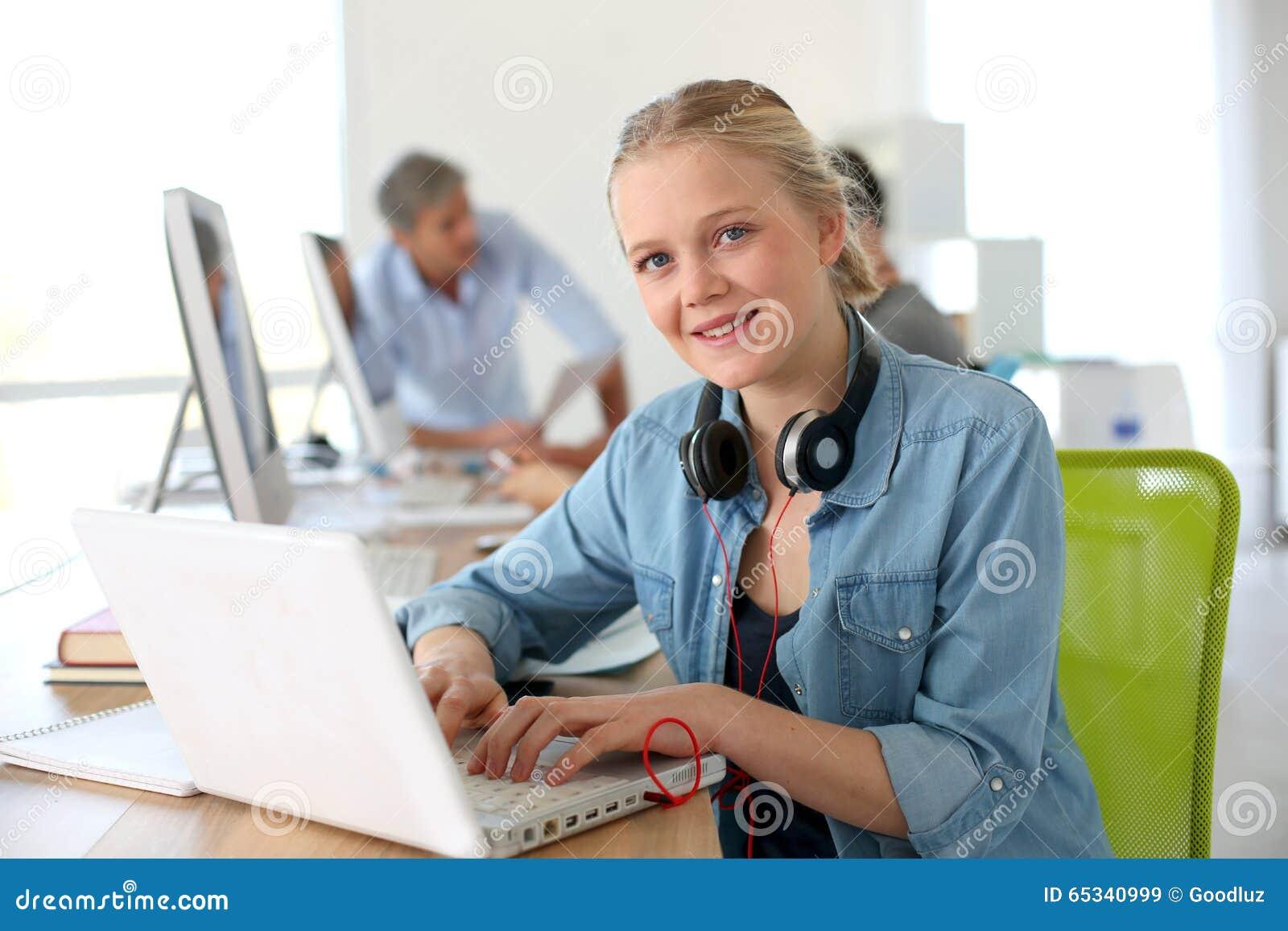 Vrolijk meisje in de gegevensverwerking van klasse die laptop met behulp van