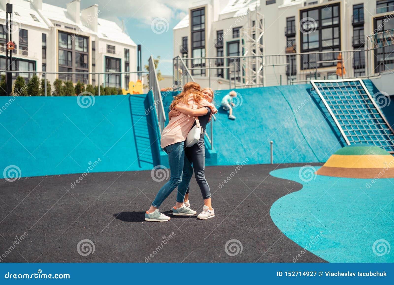 Vrolijk meisje die haar mum vast op een sportengrond koesteren
