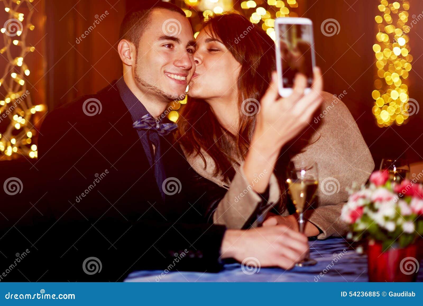 Vrolijk meisje die haar vriend op de wang kussen terwijl het nemen van zelfportret