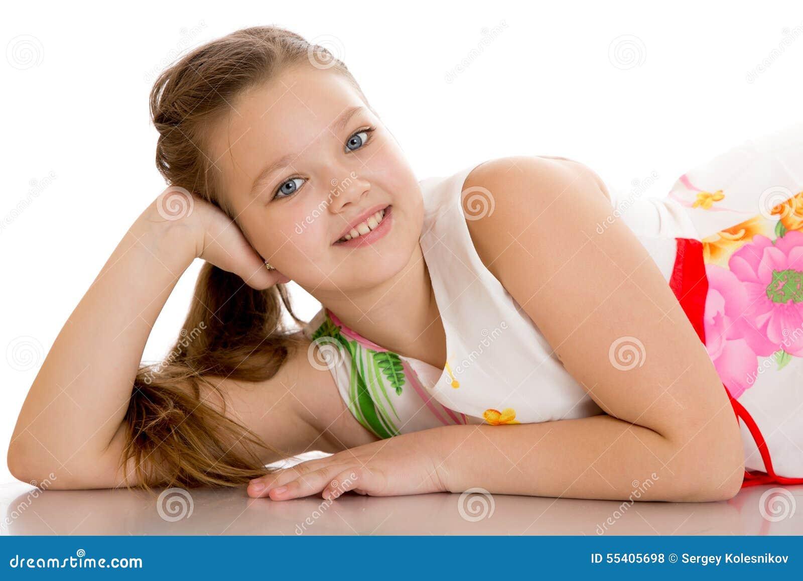Vrolijk meisje die op de vloer liggen