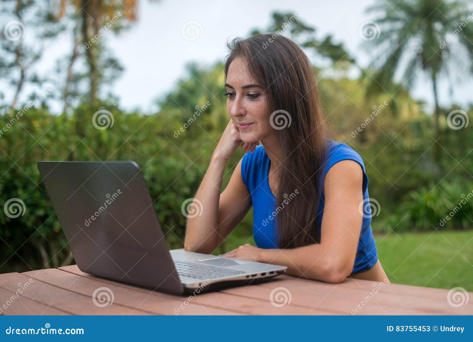 Vrolijk meisje die op online video op laptop computerzitting letten in het park