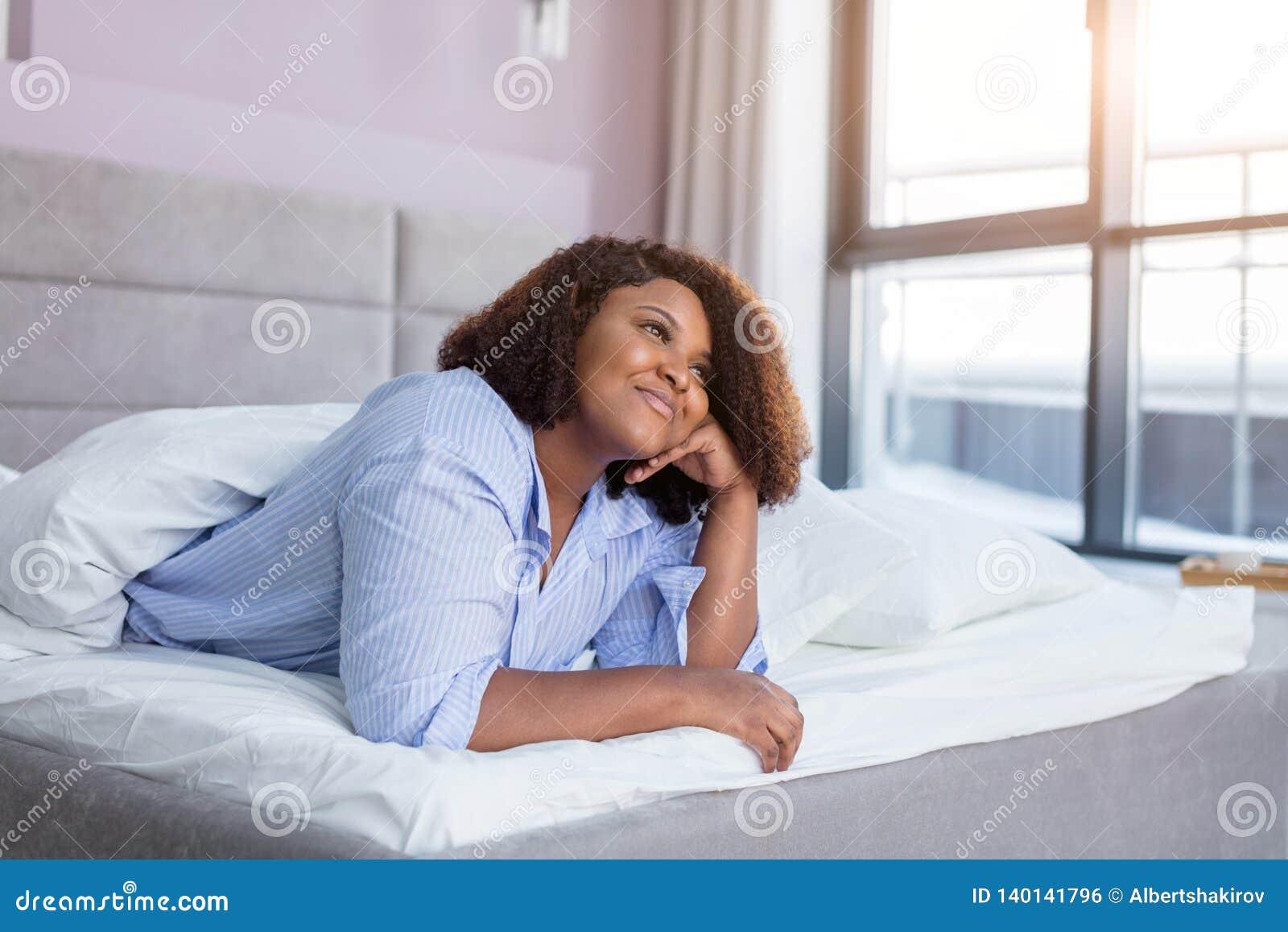 Vrolijk meisje die over haar vriend denken terwijl het rusten in het comfortabele bed