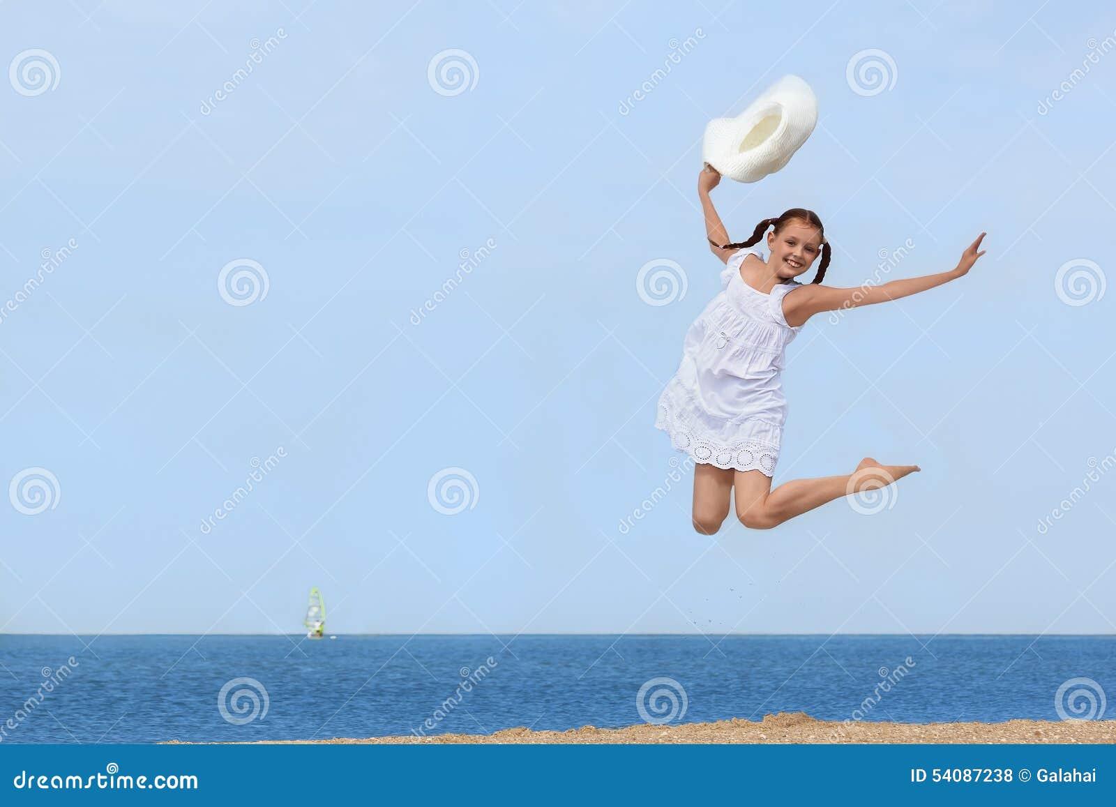 Vrolijk meisje die over het water bij het strand springen