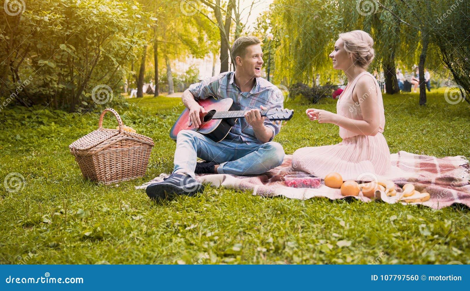 Vrolijk meisje die vreugdevol liederen met haar vriend het spelen gitaar zingen, datum