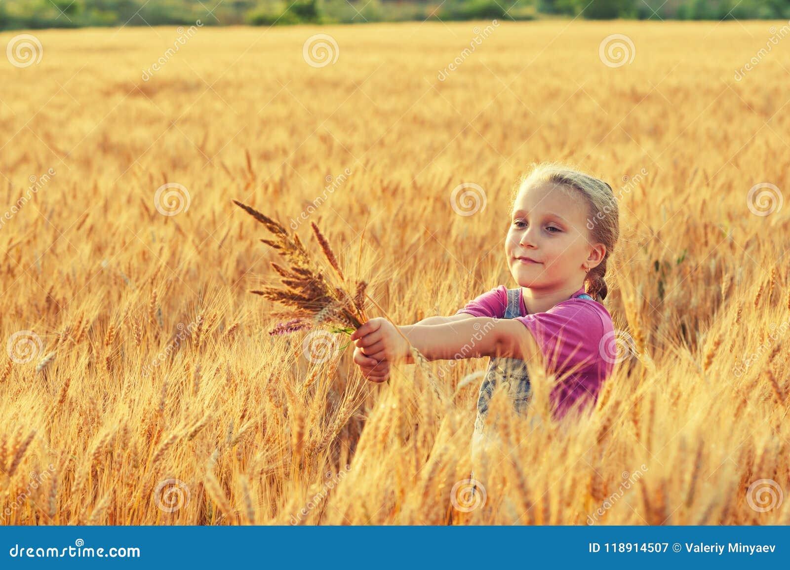 Vrolijk meisje op een gang dichtbij het gebied met tarwe