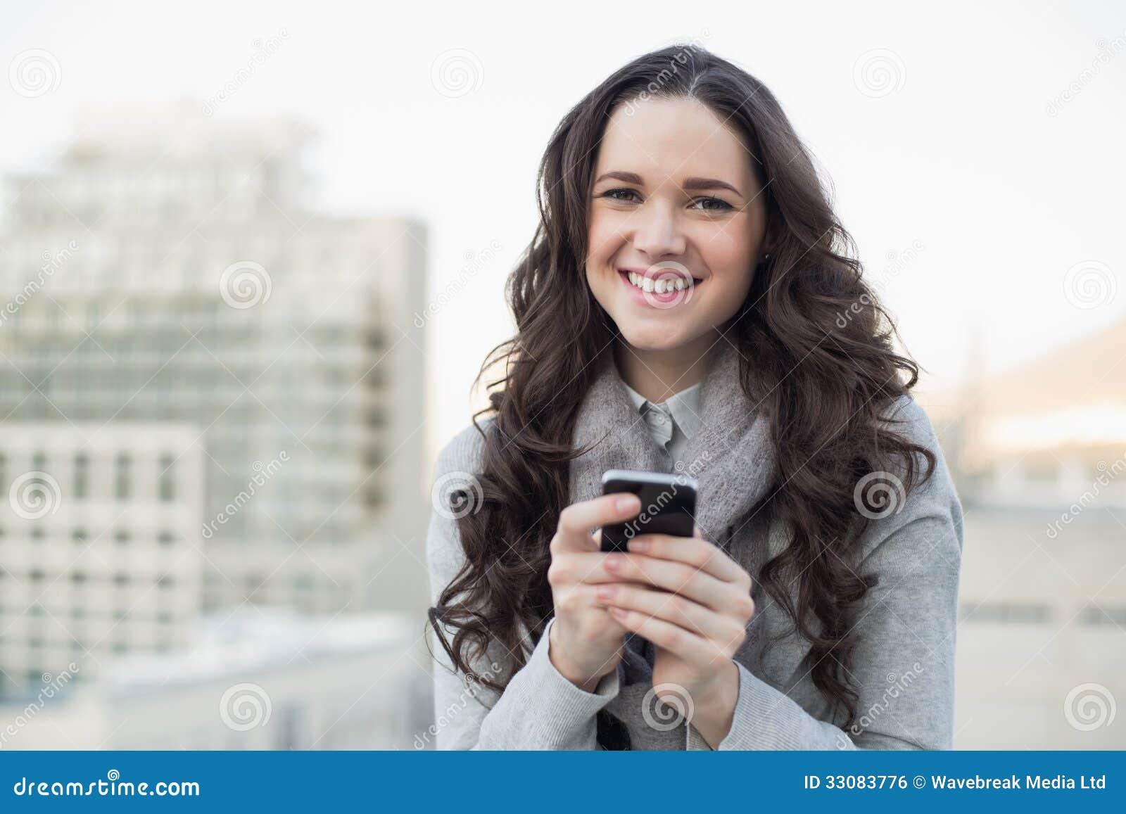 Vrolijk mooi brunette die een tekst op haar smartphone verzenden