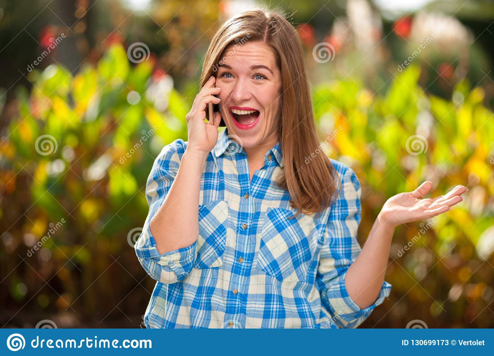 Vrolijk mooi jong meisje die op de telefoon spreken
