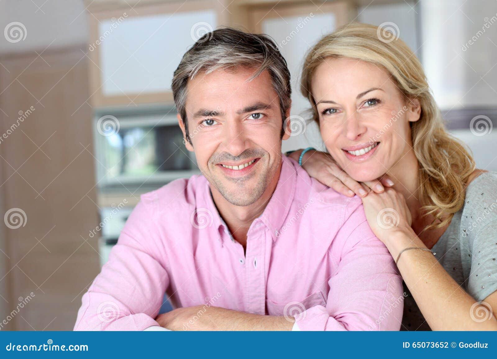 Vrolijk paar die in de keuken glimlachen