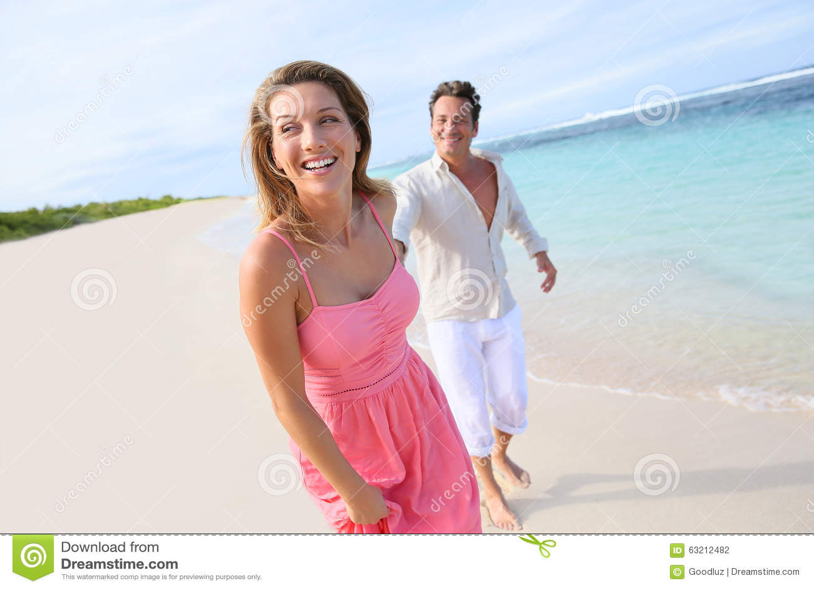 Vrolijk paar die op het strand lopen