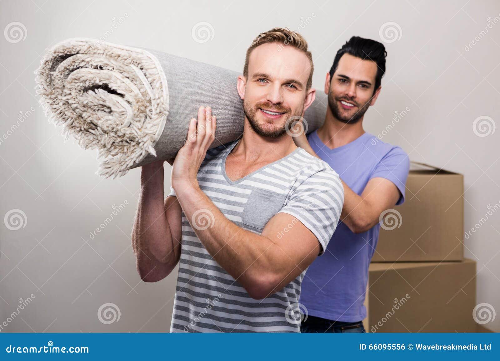 Vrolijk paar die opgerold tapijt dragen