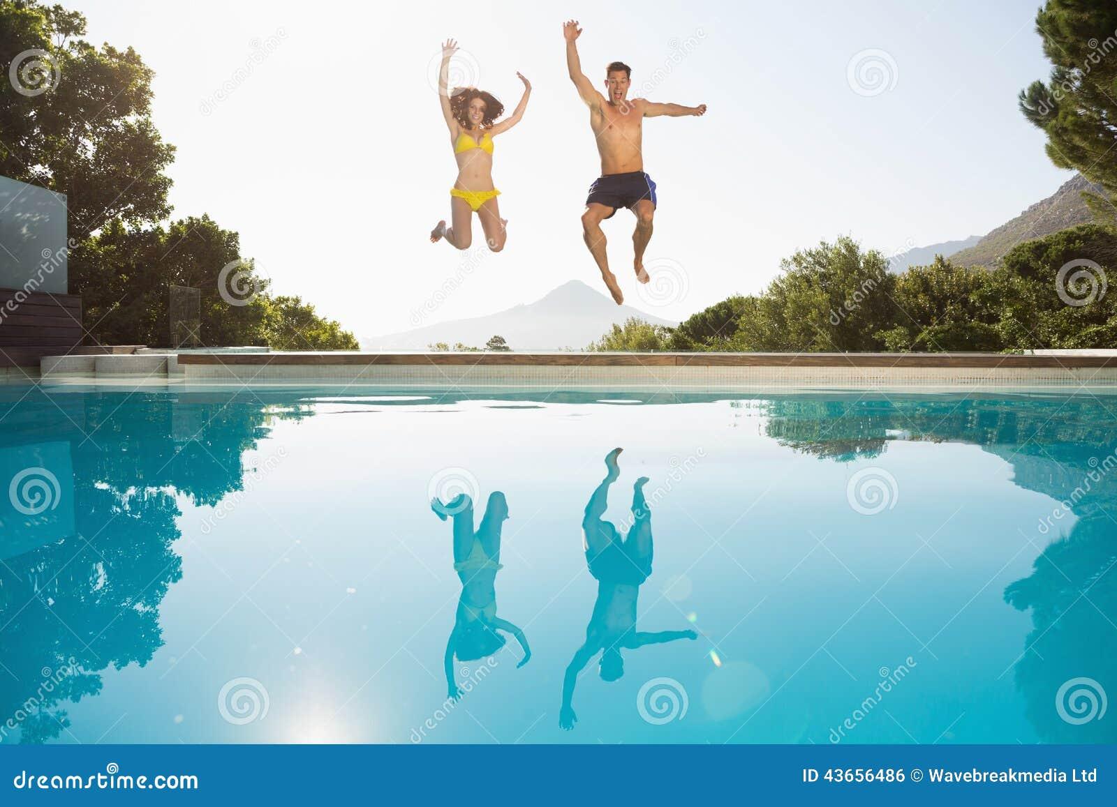 Vrolijk paar die in zwembad springen
