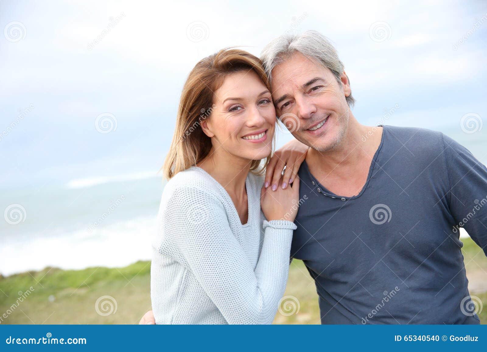 Vrolijk paar op middelbare leeftijd door de kust