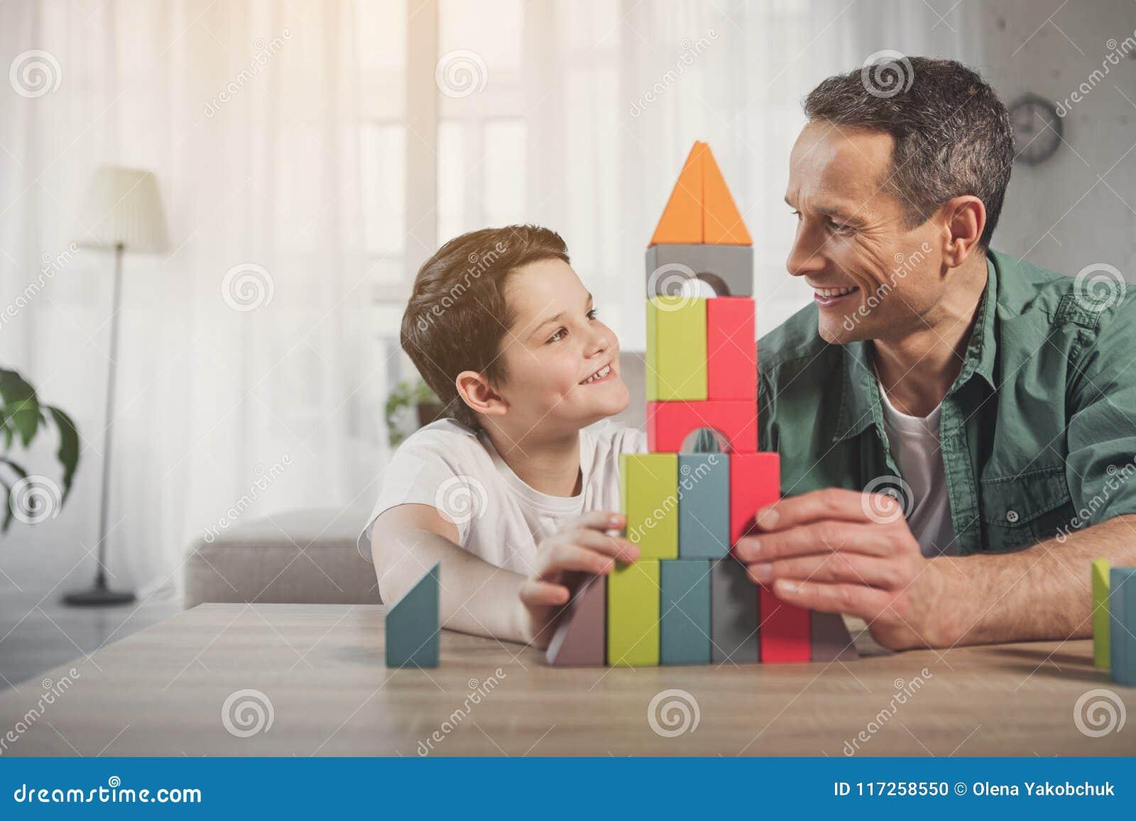 Vrolijk papa en jong geitje die van spel thuis genieten