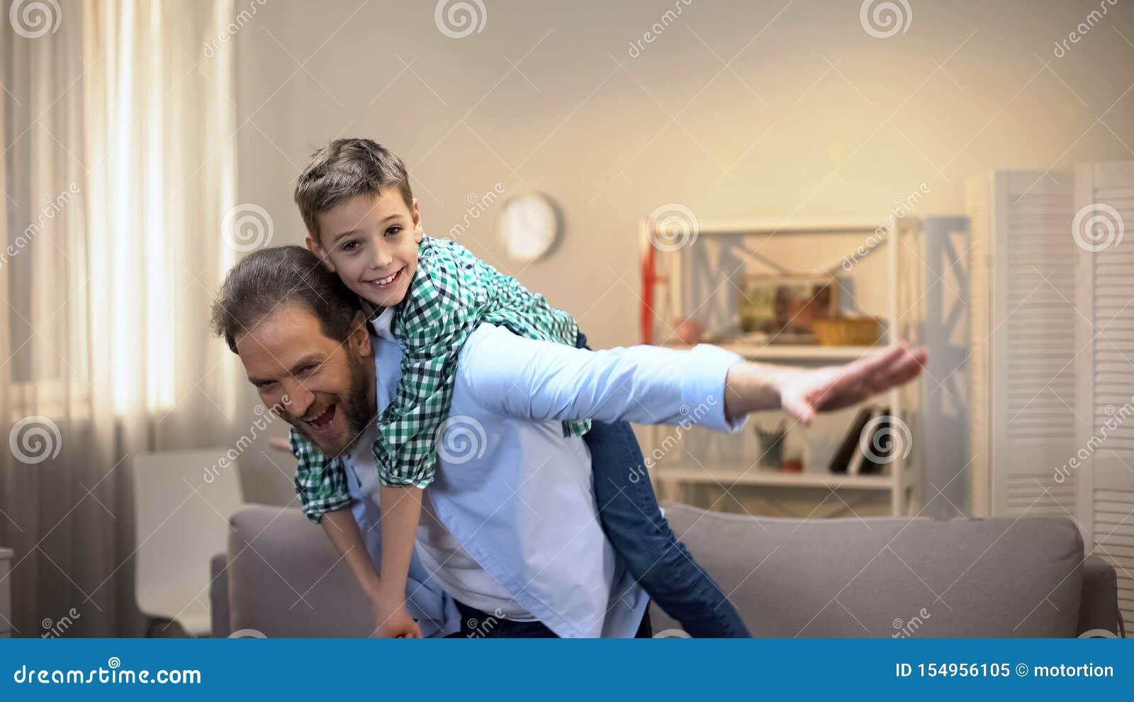 Vrolijk papa en zoons het spelen vliegtuig, gelukkige familieogenblikken, kinderjaren