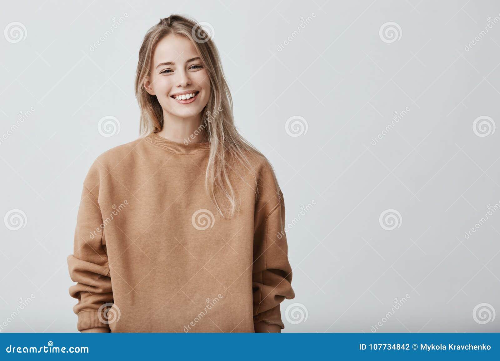 8aed1489df6f5e Vrolijk positief vrouwelijk kereltje met terloops gekleed blondehaar, blij  om graduatiegelukwensen van te ontvangen