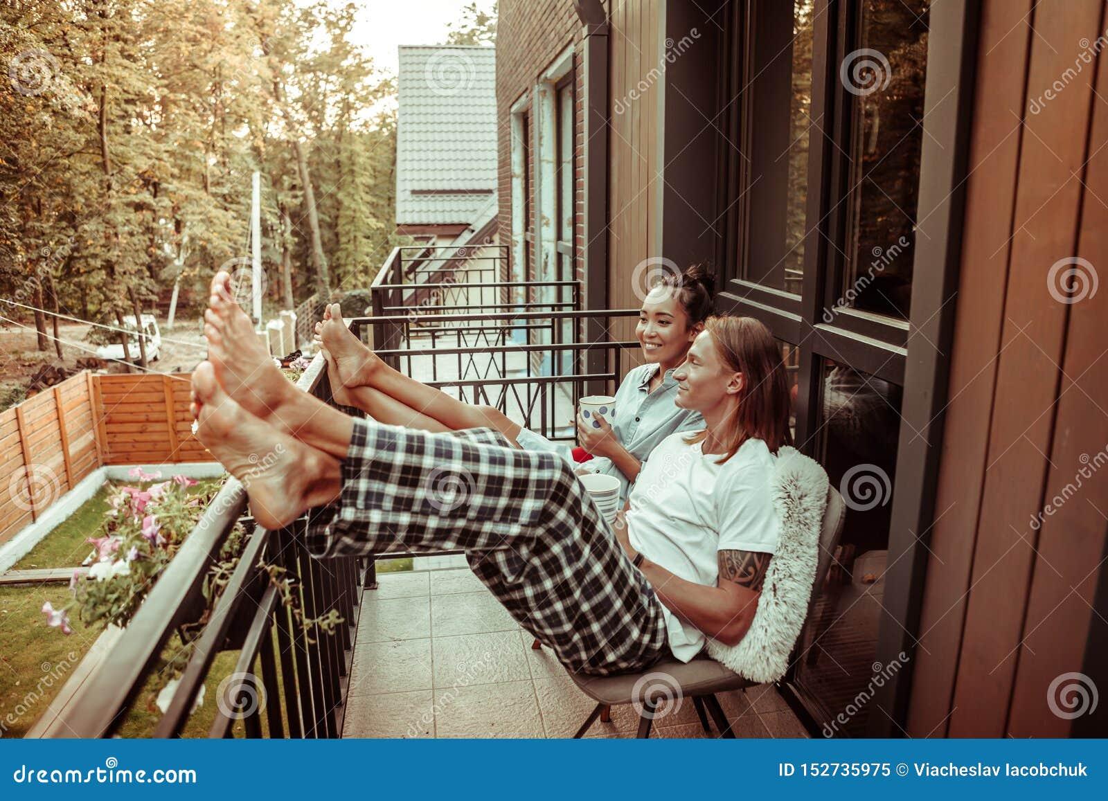Vrolijk vriendschappelijk paar die op het metaaltraliewerk leunen op een balkon