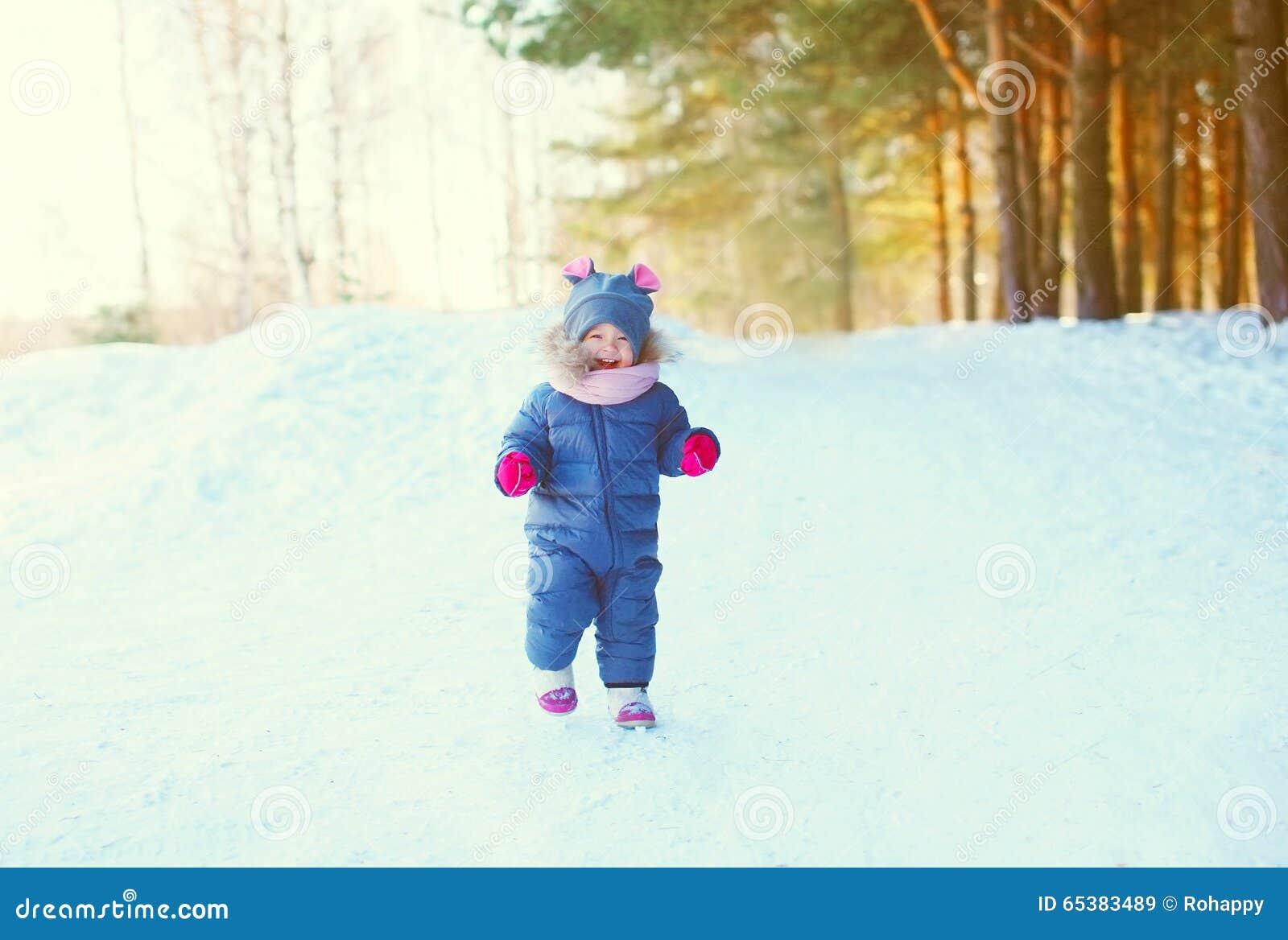 Vrolijk weinig kind die op sneeuw in de winter spelen