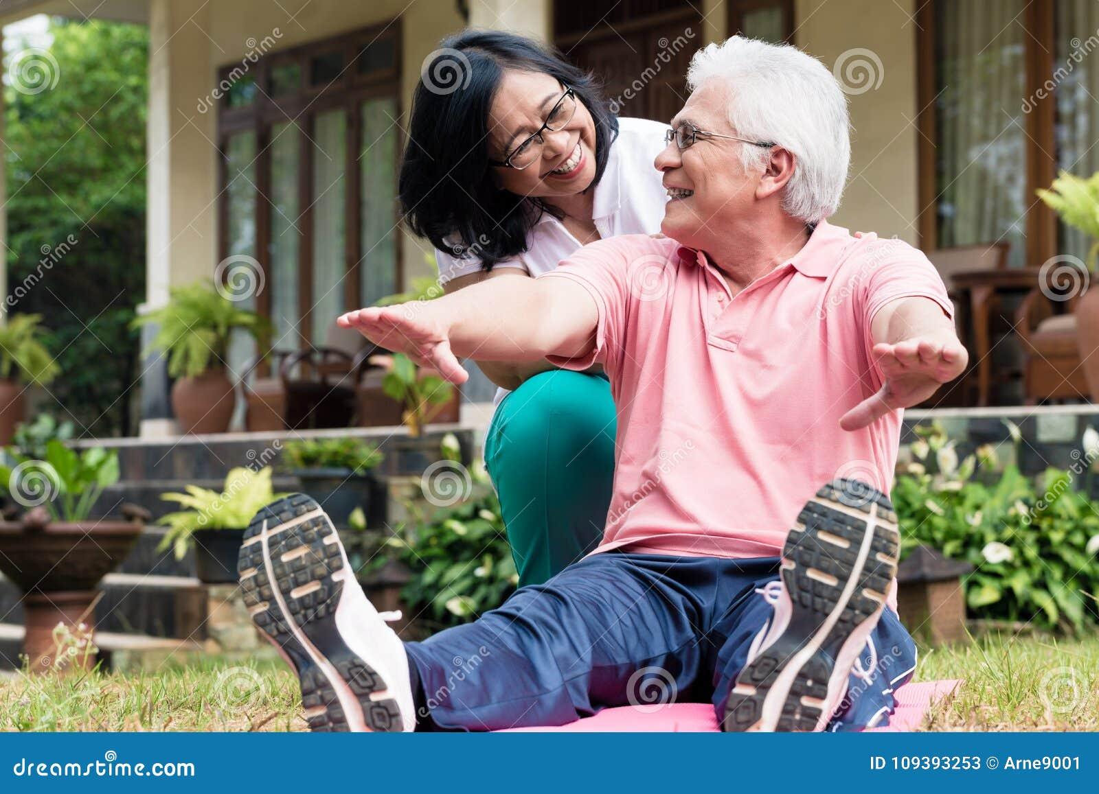 Vrolijke hogere vrouw die haar partner helpen tijdens trainingzitting