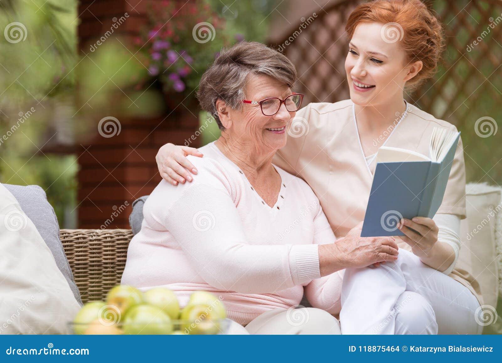 Vrolijke hogere vrouw met haar tedere huisbewaarder die een boek t lezen