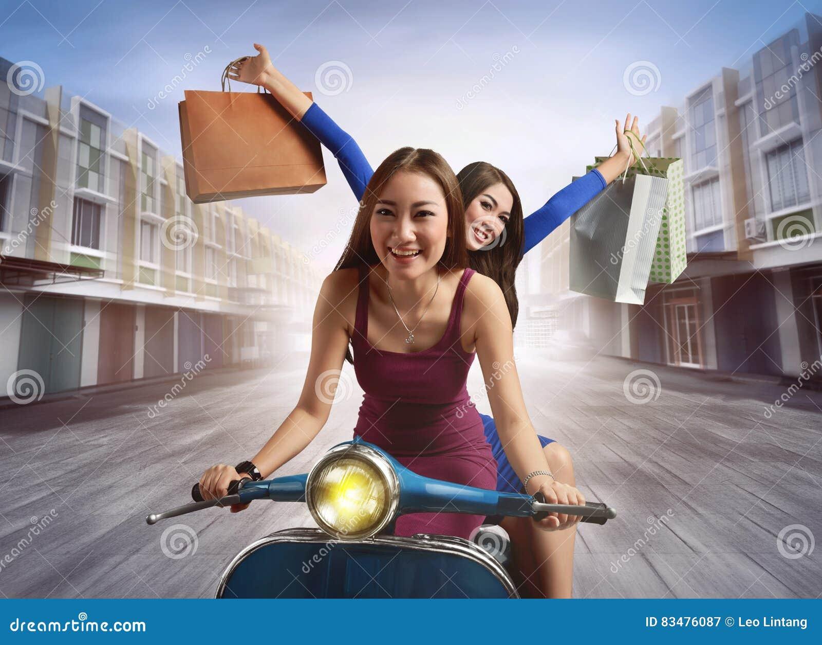 Vrolijke jonge Aziatische vrouw twee met het winkelen zak die een scoote berijdt
