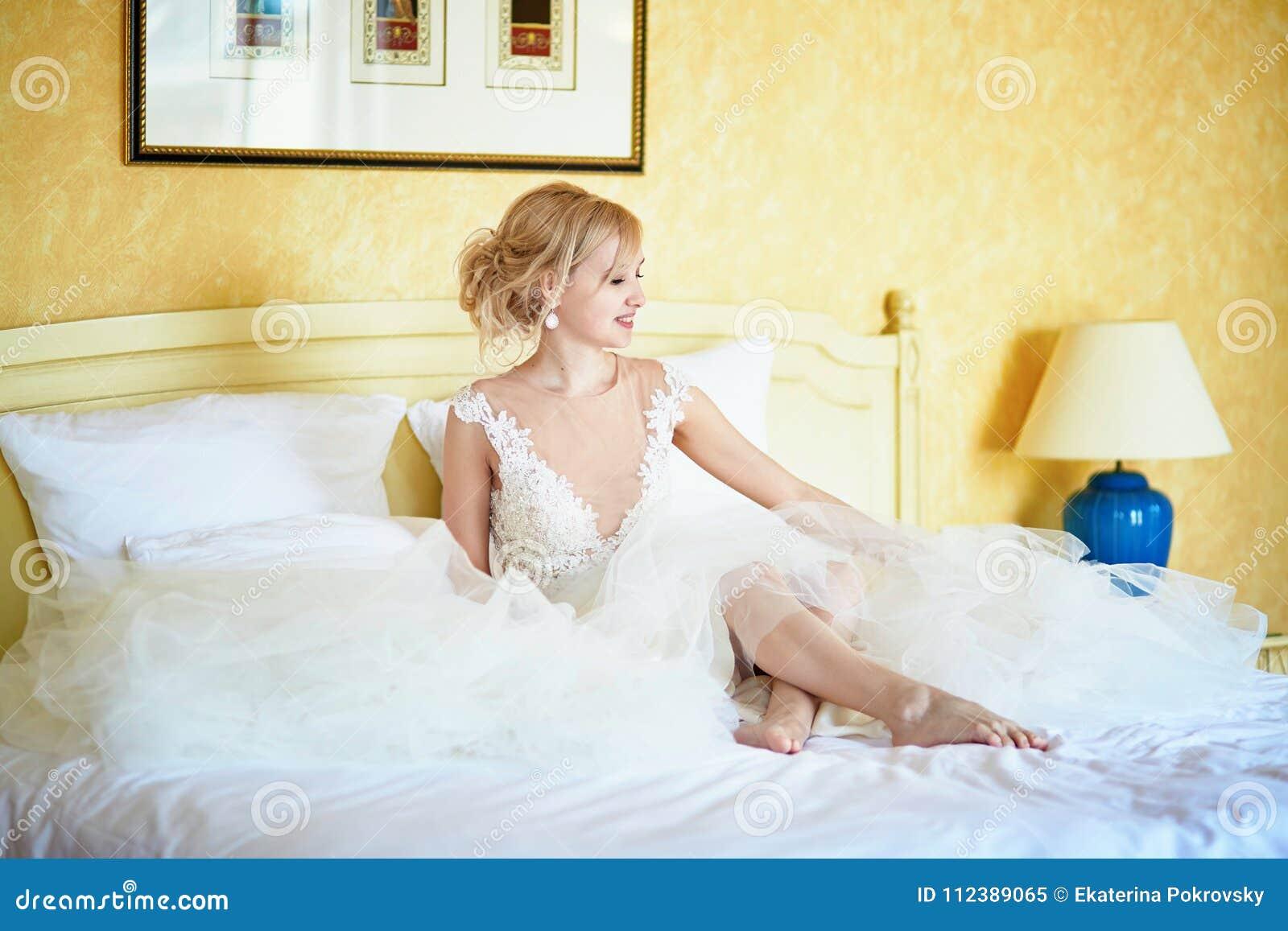 Vrolijke jonge bruid in huwelijkskleding in hotelruimte