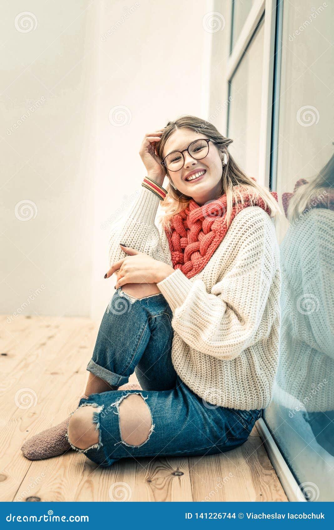 Vrolijke jonge damezitting op houten vloer dichtbij het venster