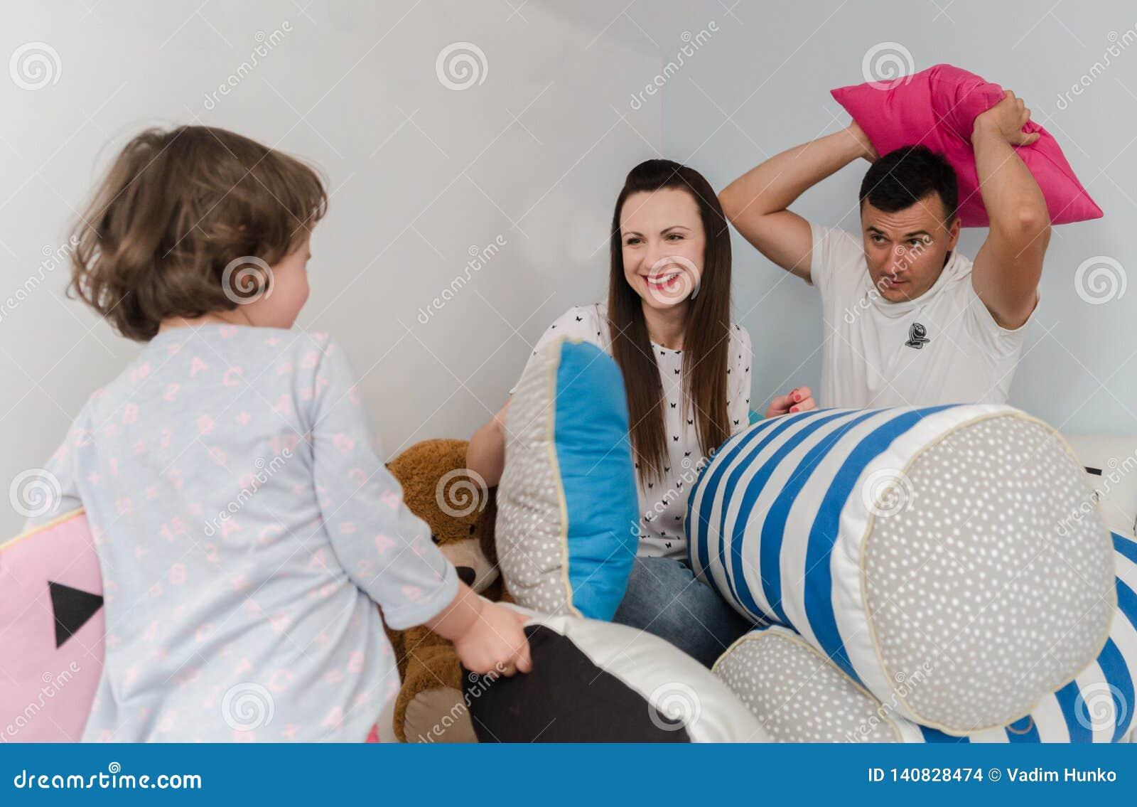 Vrolijke jonge geitjes en ouders die hoofdkussenstrijd op bed hebben thuis