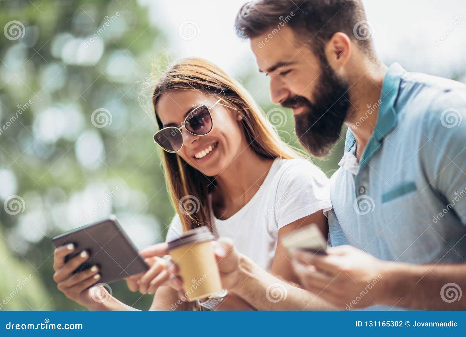 Vrolijke jonge paarzitting op een parkbank en gebruik een digitale tablet