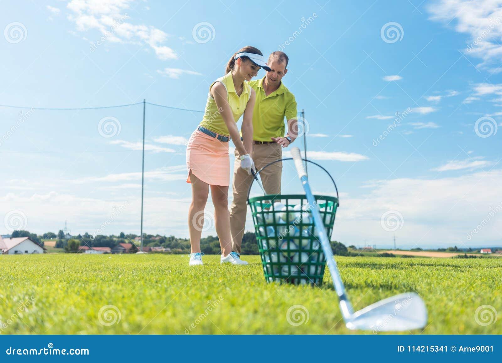 Vrolijke jonge vrouw die de correcte greep en de beweging voor het gebruiken van de golfclub leren