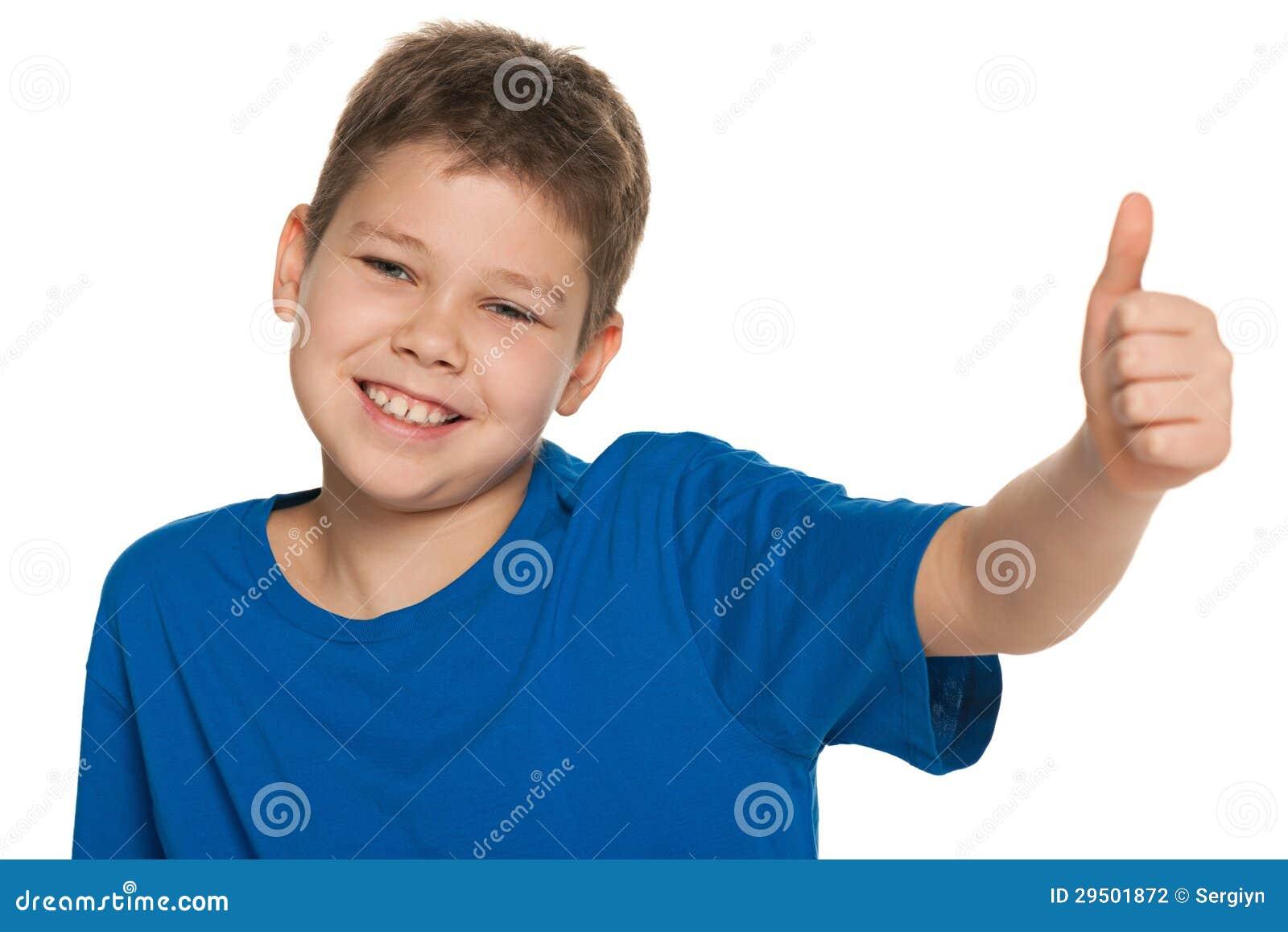 Vrolijke jongen die in blauw overhemd zijn duim tegenhouden