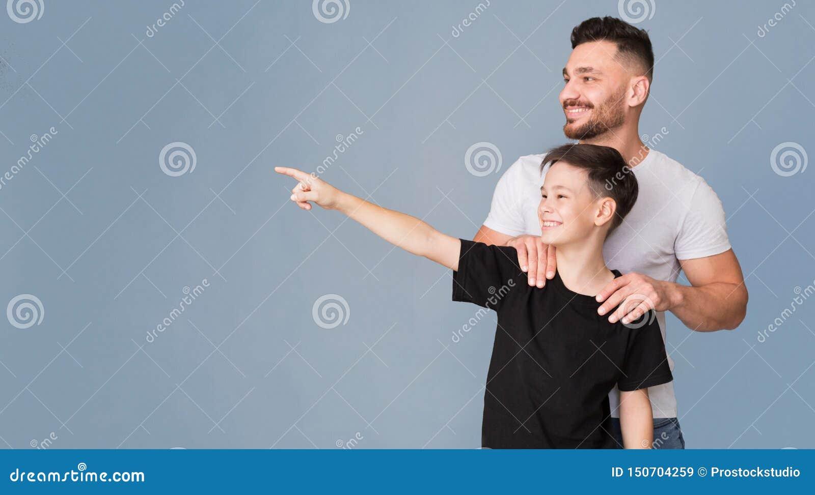 Vrolijke jongen die iets voor zijn papa tonen, die met vinger richten