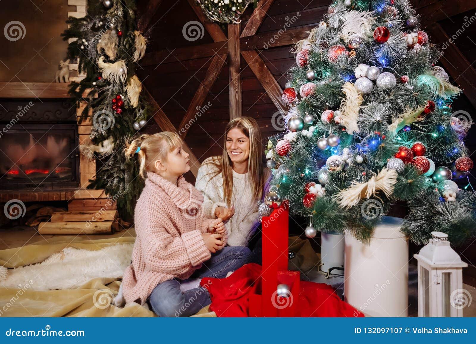 Vrolijke Kerstmis en Gelukkig Nieuwjaar Het mamma en de dochter verfraaien binnen de Kerstboom Houdende van familie dicht omhoog