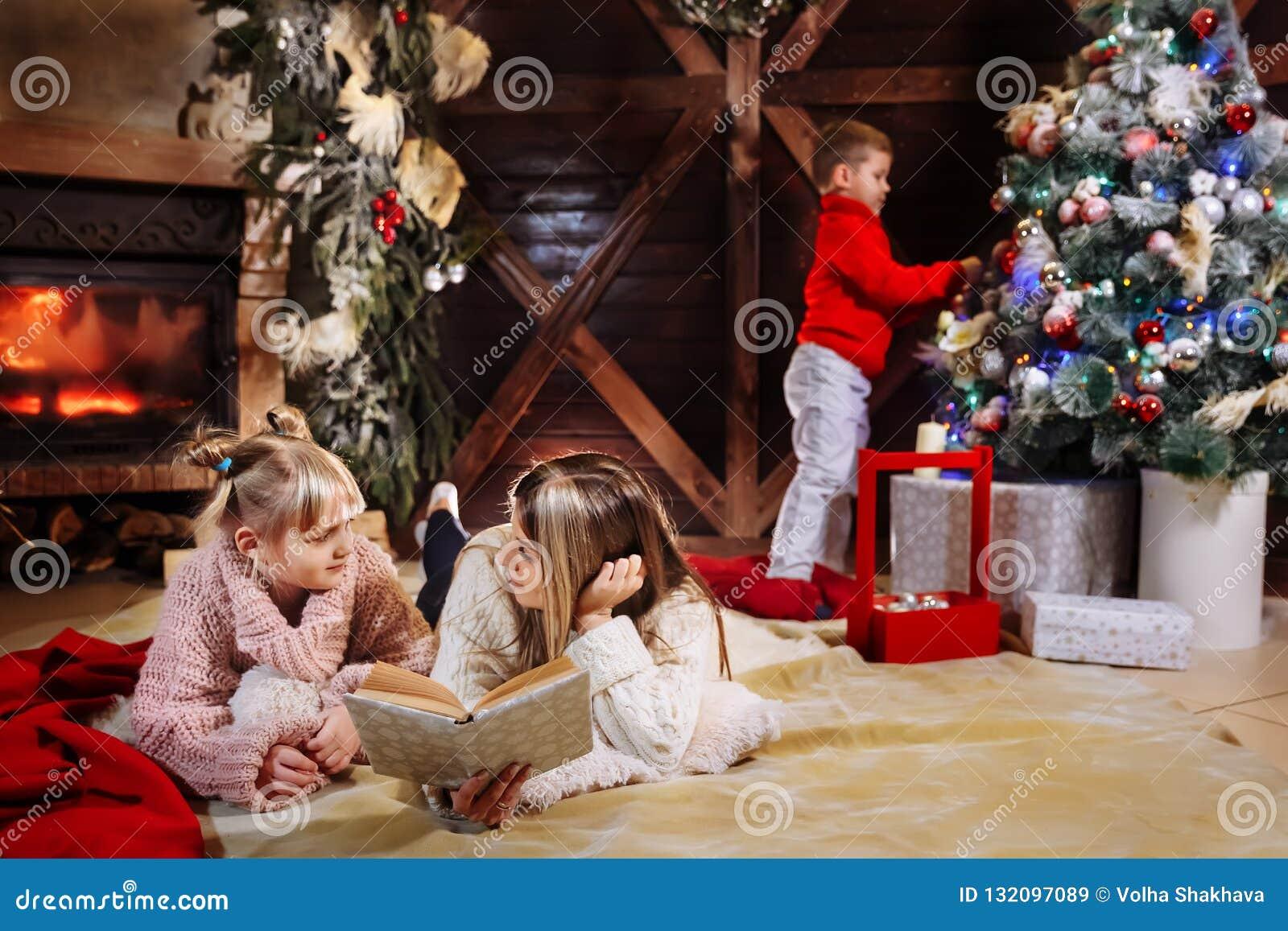 Vrolijke Kerstmis en Gelukkig Nieuwjaar Mooie familie in Kerstmisbinnenland Vrij jonge moeder die een boek lezen aan haar
