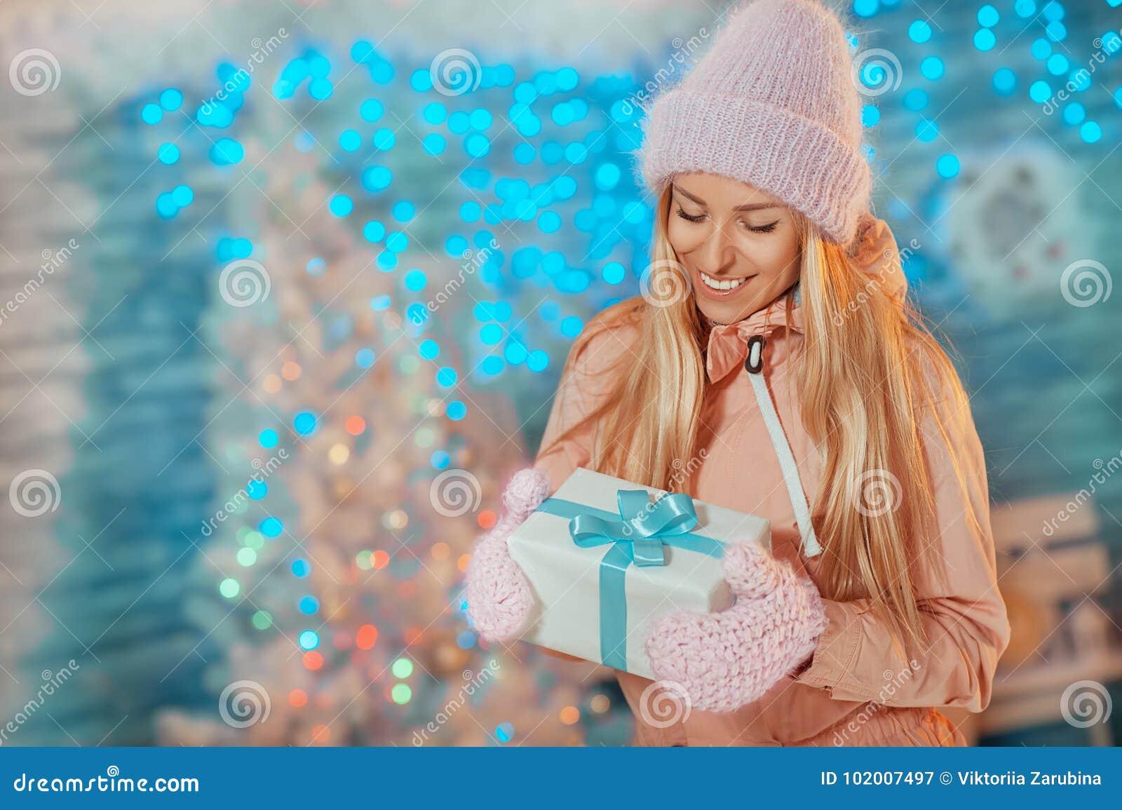 Vrolijke Kerstmis en Gelukkig Nieuwjaar! Portret van gelukkige vrolijke mooie vrouw die in gebreide hoedenvuisthandschoenen vakan