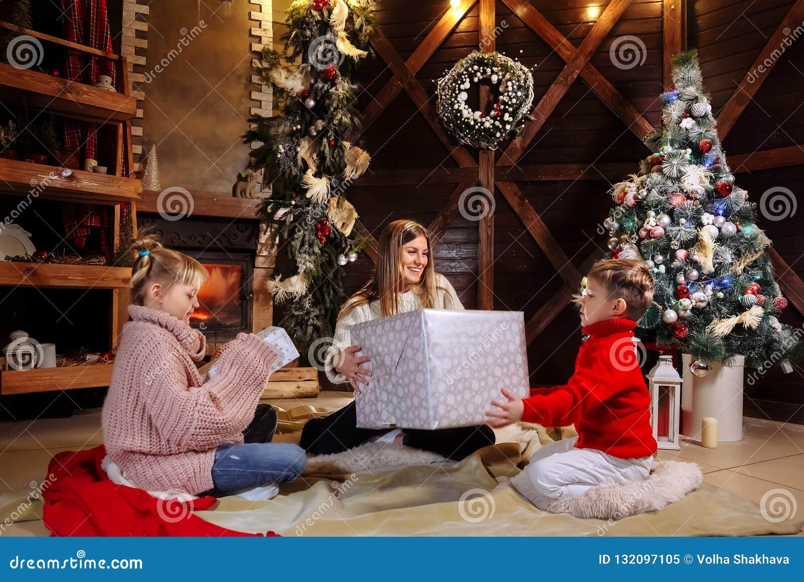 Vrolijke Kerstmis en Gelukkig Nieuwjaar Vrolijk mamma en haar leuke dochter en zoon die giften ruilen Ouder en kinderen