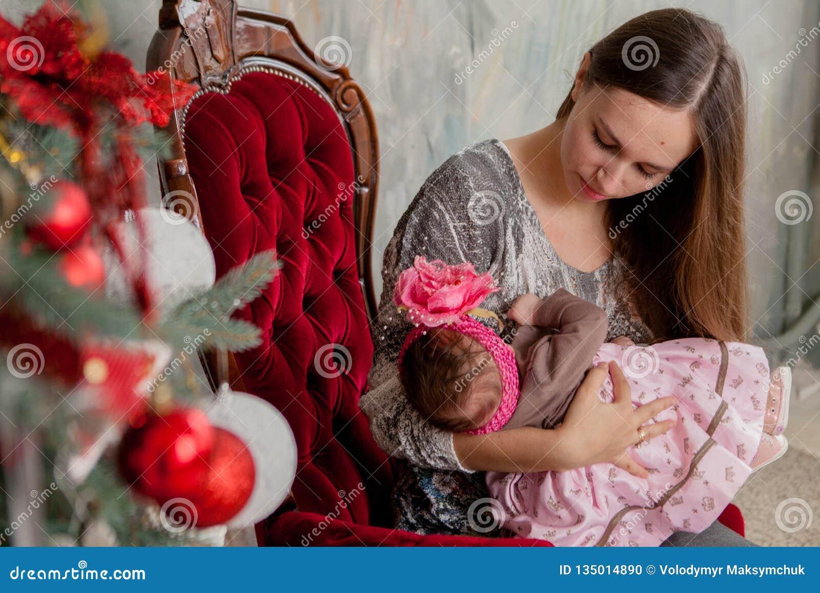Vrolijke Kerstmis en Gelukkig Vakantie vrij jong mamma die een boek binnen lezen aan haar leuke dochter dichtbij Kerstboom