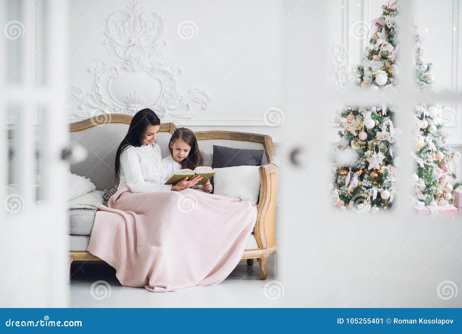 Vrolijke Kerstmis en gelukkige vakantie Vrij jong mamma die een boek binnen lezen aan haar leuke dochter dichtbij Kerstboom