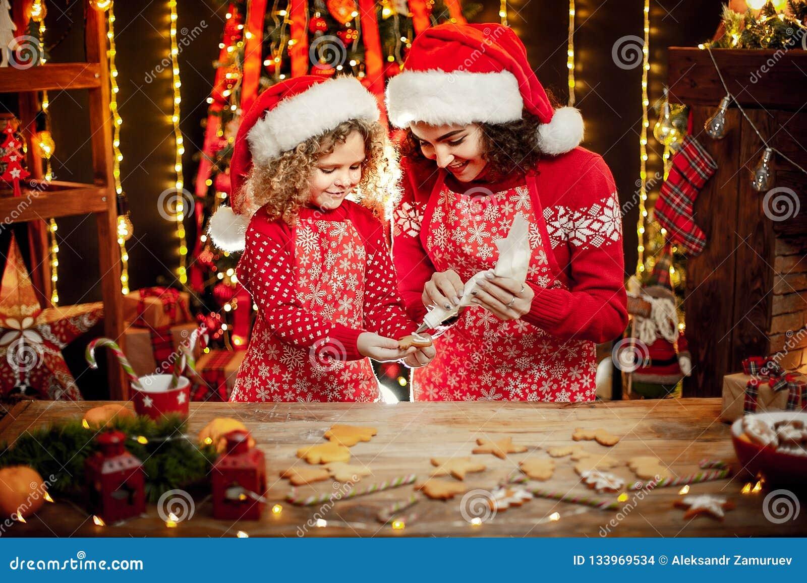 Vrolijke Kerstmis en gelukkige vakantie Vrolijk leuk krullend meisje en haar oudere zuster in santashoeden het koken