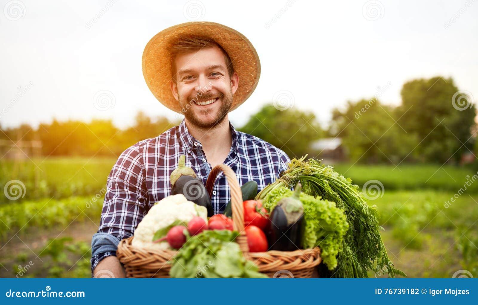 Vrolijke landbouwer met organische groenten