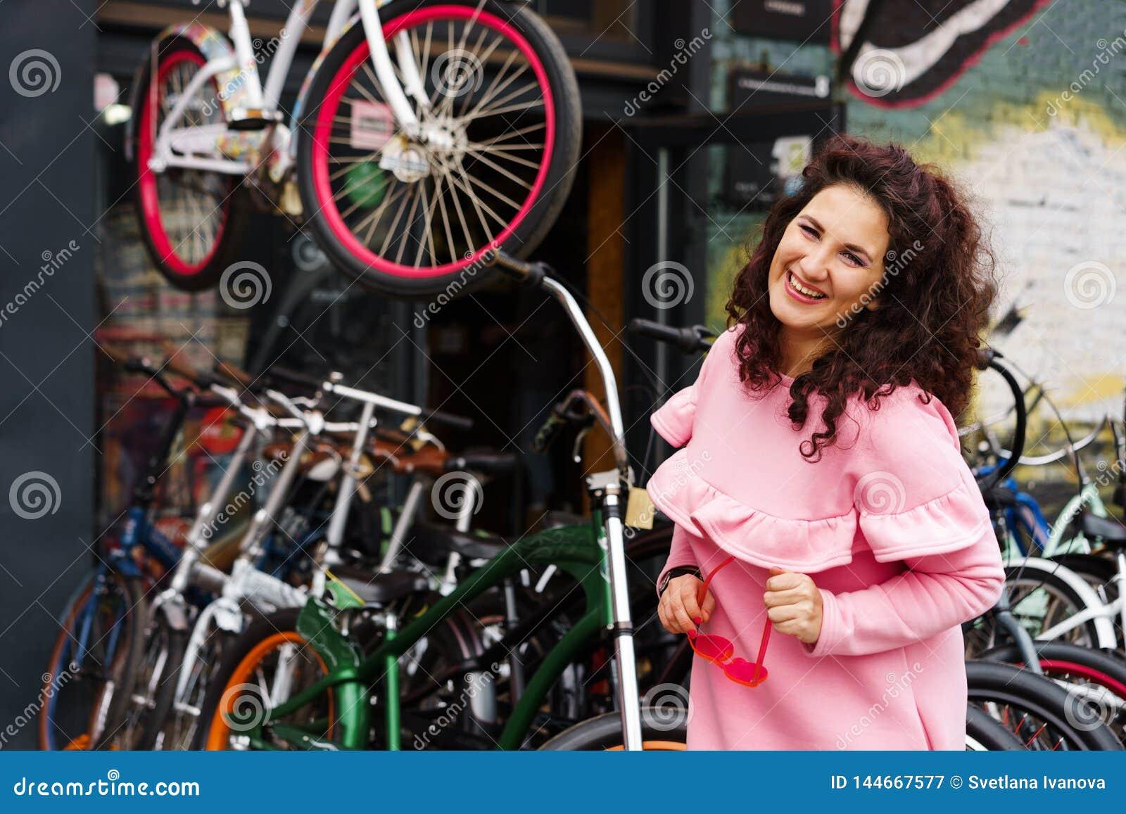 Vrolijke langharige donkerbruine vrouw in een roze kleding bij een fietswinkel