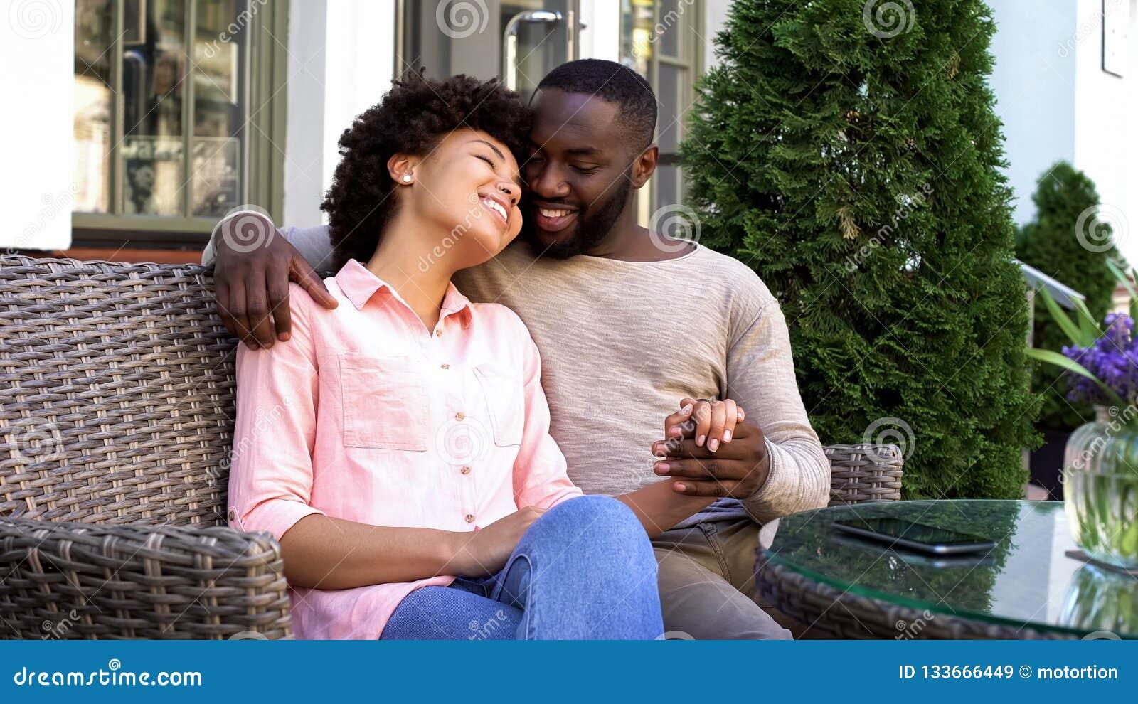 Vrolijke man en vrouw die van romantische datum genieten, die bij koffie, verhouding zitten