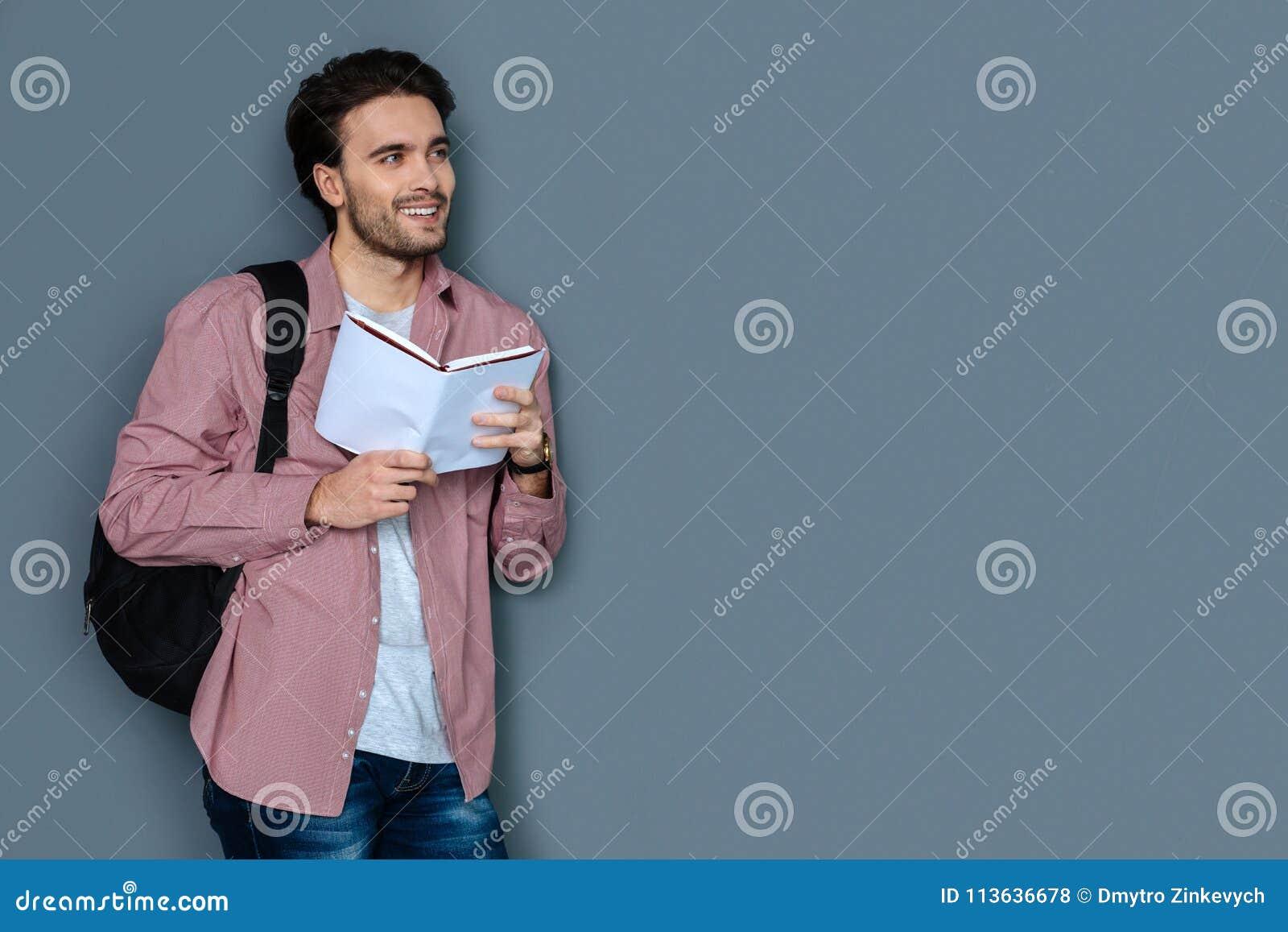 Vrolijke mannelijke toerist die een reisgids lezen
