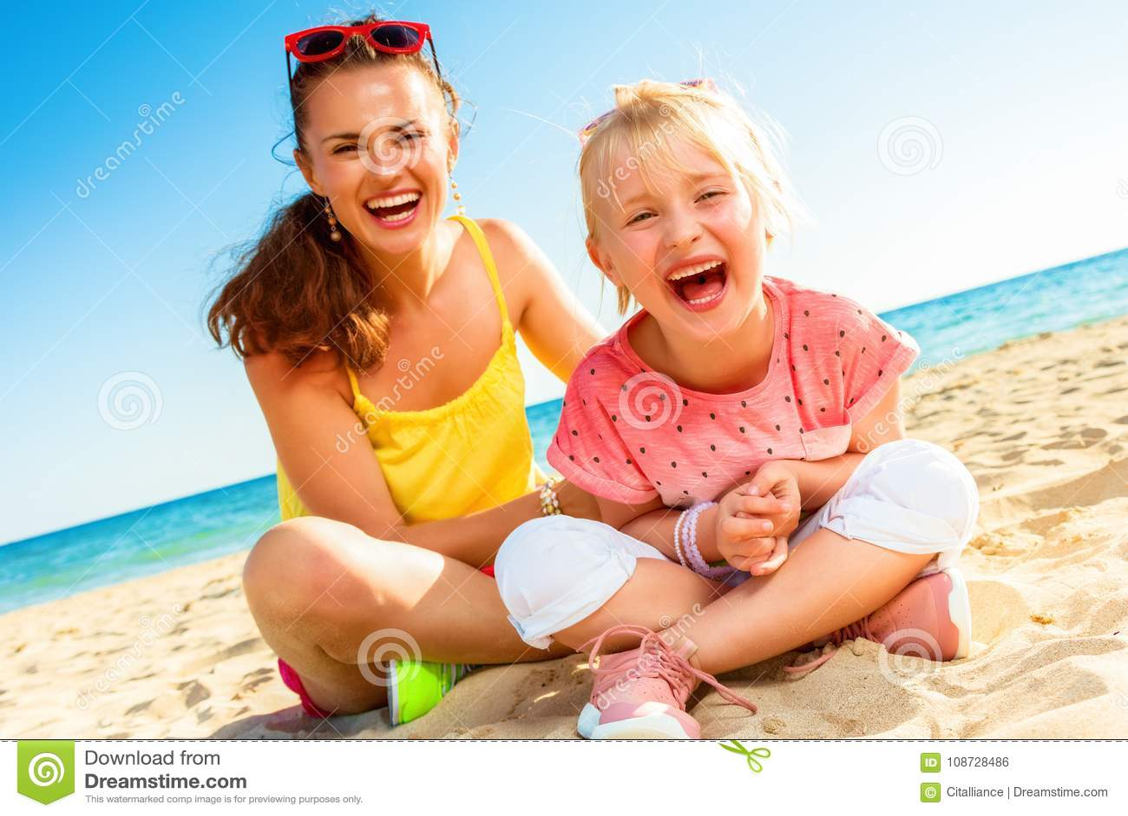 Vrolijke moderne moeder en kindzitting op strand