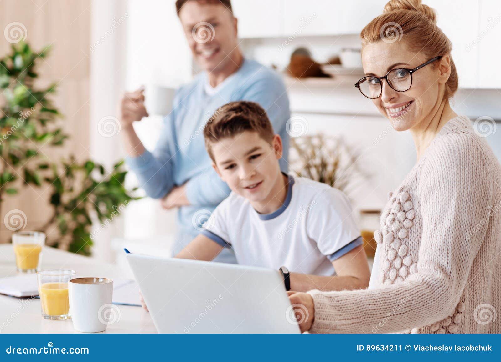 Vrolijke moeder die haar zoon met thuiswerk helpen
