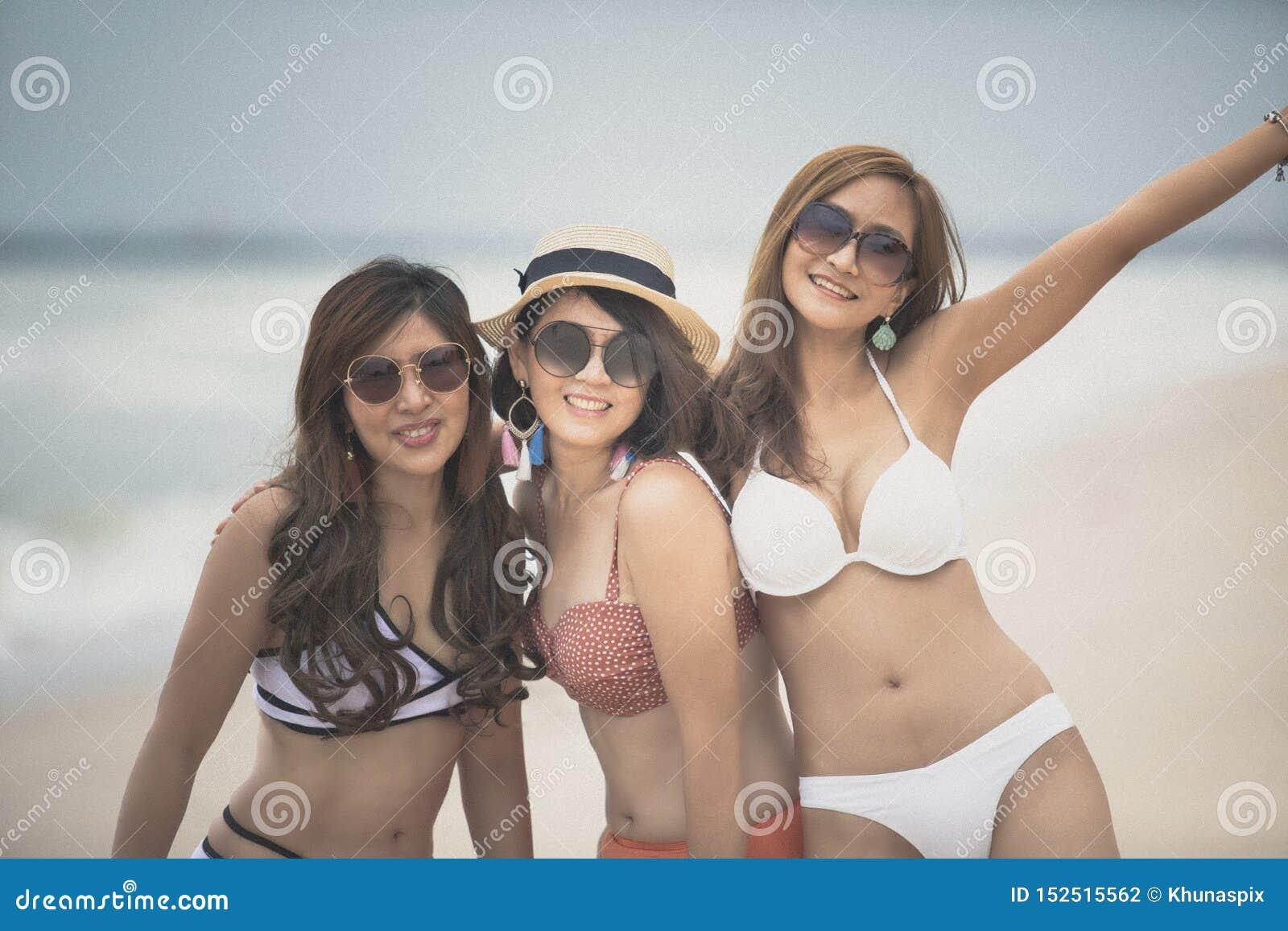 Vrolijke mooie Aziatische vrouw die zwempak toothy het glimlachen gezichtsgeluk dragen bij kust