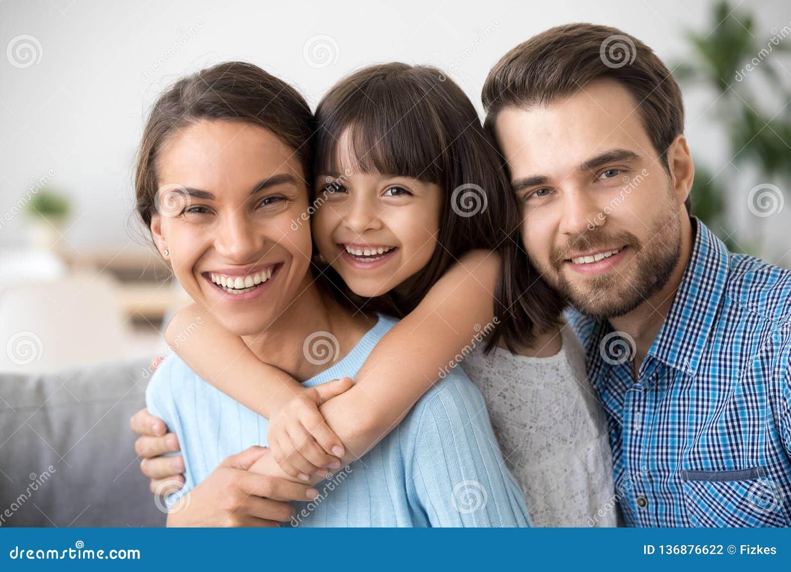 Vrolijke mooie familie van drie die het lachen het bekijken omhelzen