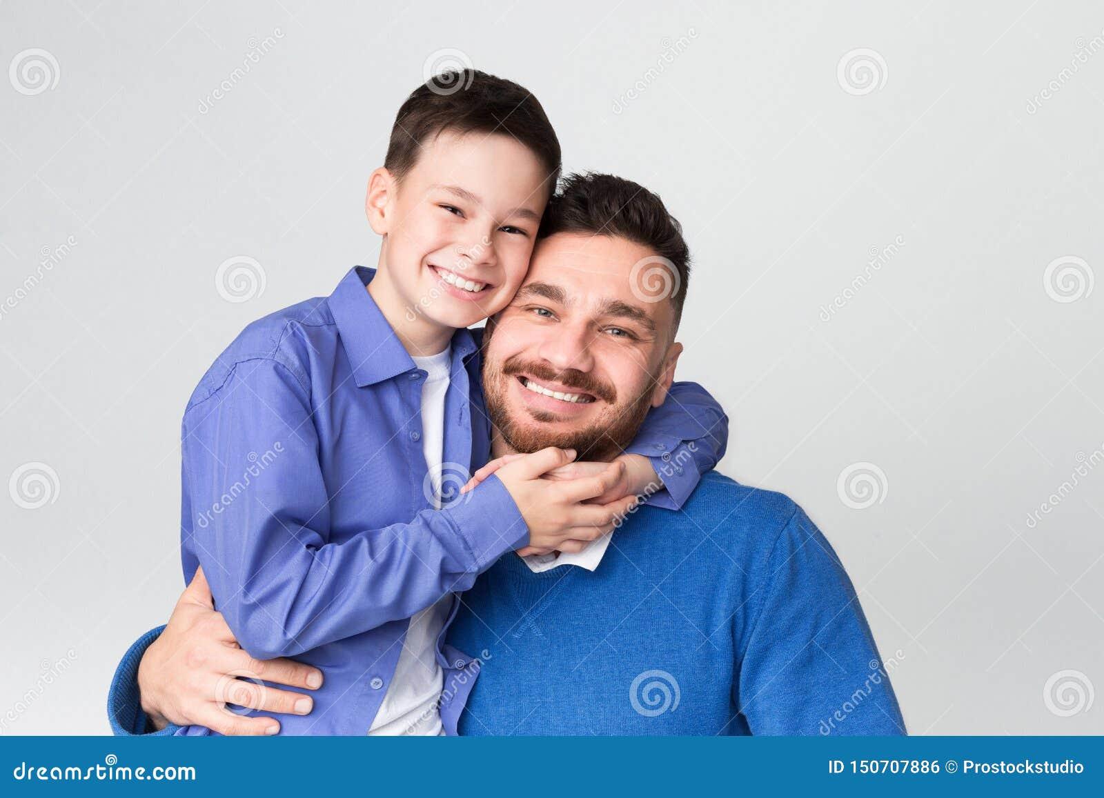 Vrolijke papa en zoon die en bij camera omhelzen glimlachen
