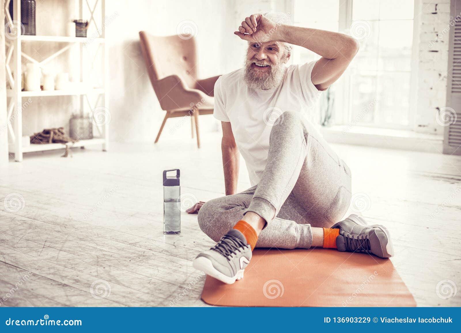 Vrolijke rijpe mens het besteden pauze op mat