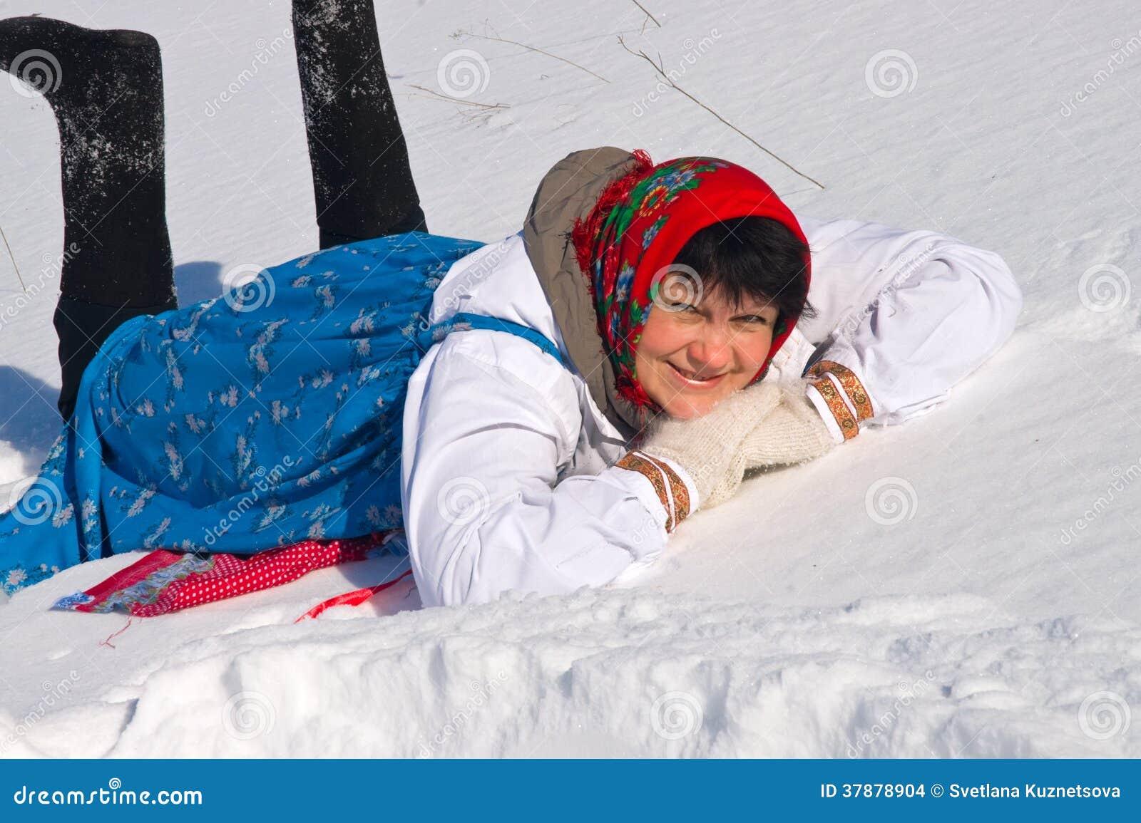 Vrolijke Russische vrouw in sundress die in de sneeuw liggen