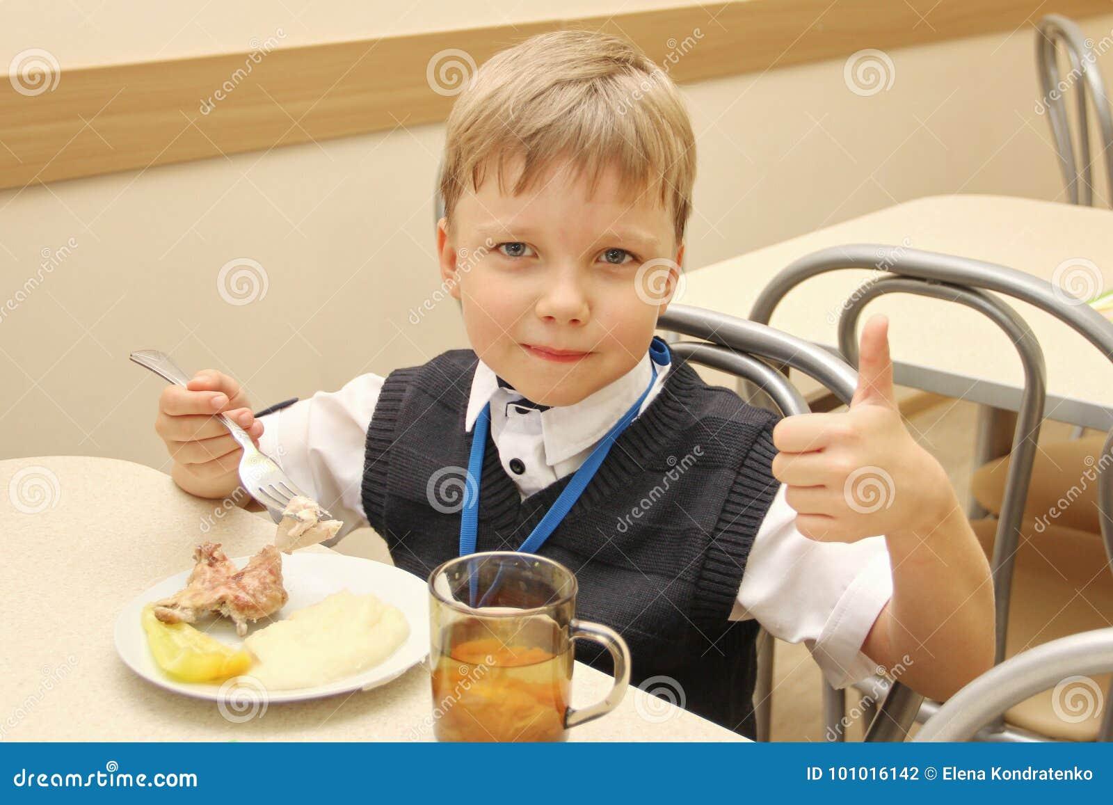 Vrolijke schooljongenzitting bij Lijst in Schoolcafetaria die Maaltijd eten het drinkende sap en toont duimen - Rusland, Moskou,